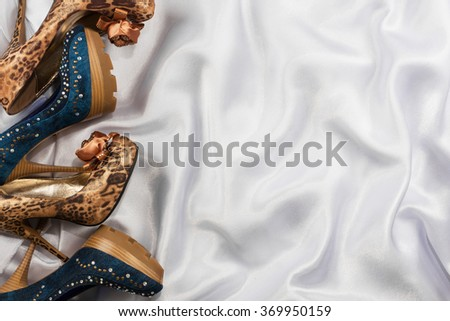 Denim and leopard shoes lying on white silk, with space for your text - stock photo