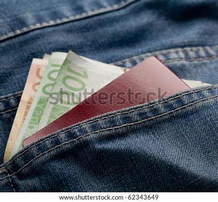 Denim detail with money and passport - stock photo
