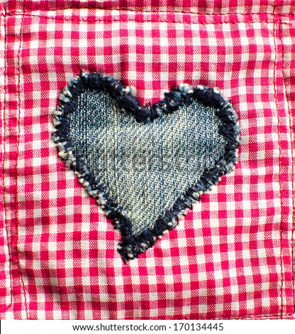 Denim heart on red cloth