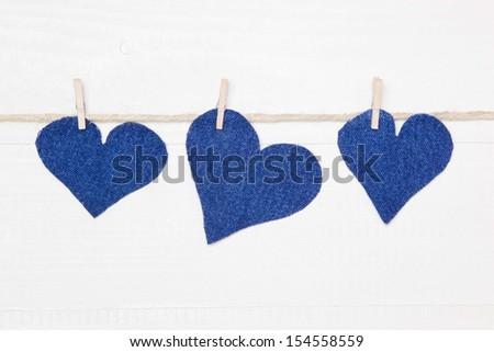 Denim hearts hanging on string - stock photo