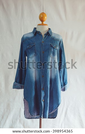 Denim jacket with a white cloth as a backdrop. - stock photo