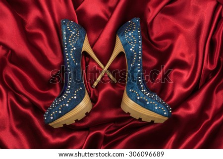 Denim shoes lying on red silk, can use as background - stock photo