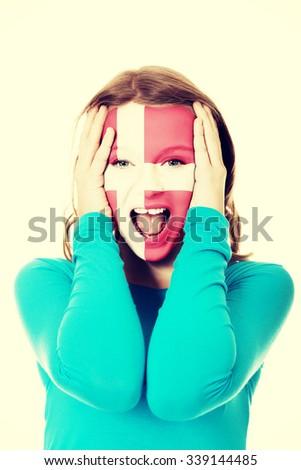Denmark flag painted on woman's face. - stock photo