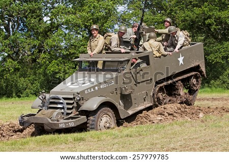 DENMEAD, UK - MAY 25: US army reenactors from the WW2 period take their halftrack into a tank ditch during a battle re-enactment for the public to watch at the Overlord show on May 25, 2014 in Denmead - stock photo