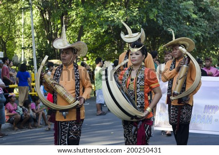 DENPASAR, BALI, INDONESIA - JUNE 18: Balinese dressed in a colorful variety in the parade in Bali Art Festival on June 18, 2014 in Denpasar, Indonesia - stock photo