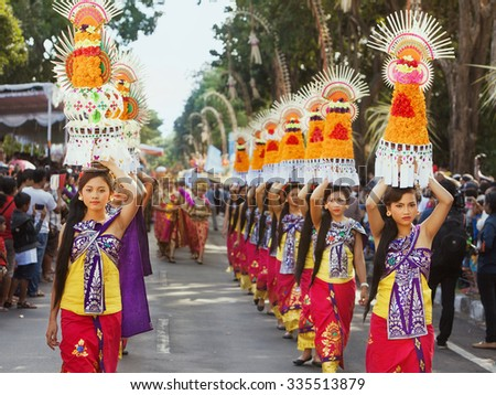 DENPASAR, BALI ISLAND, INDONESIA - JUNE 13, 2015: Group of beautiful women dressed in traditional Balinese costumes carry on head religious offering for hindu ceremony on parade at Bali Art Festival. - stock photo