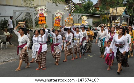 DENPASAR, BALI - MAY 12: A street procession of local village women carrying offerings on their heads for a Ngaben or cremation ceremony in Ubud, Bali, Denpasar, Indonesia on May 12, 2013.