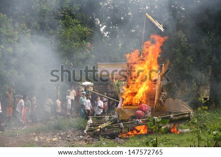 DENPASAR, INDONESIA - MAY 12:  The funeral pyre of the coffin burning with local village people during a Balinese Ngaben or cremation ceremony in Ubud, Denpasar, Bali, Indonesia on May 12, 2013. - stock photo
