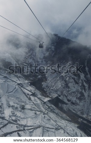 dense fog scenery cable car aerial view in winter mountain, misty outdoor cable-car hang on wire - stock photo