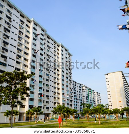 Dense of HDB housing flats with sun drying hanging clothes line in Singapore at sunset with warm and soft light. Urban concept - stock photo