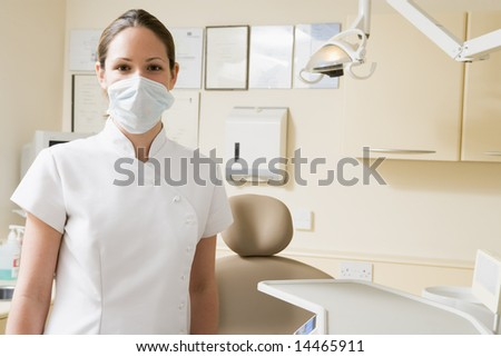 Dental assistant in exam room with mask on - stock photo