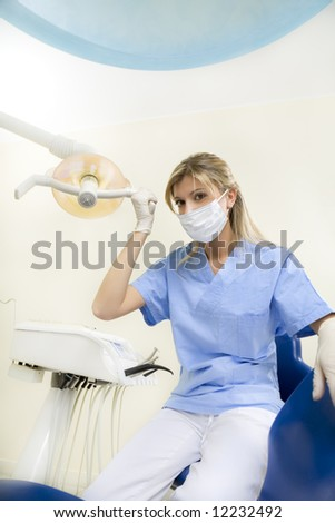 dental assistant smiling and adjusting the lamp - stock photo