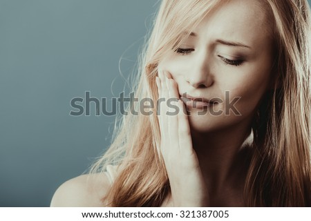 Dental care and toothache. Closeup young woman face worried girl suffering from tooth pain gray blue wall background - stock photo