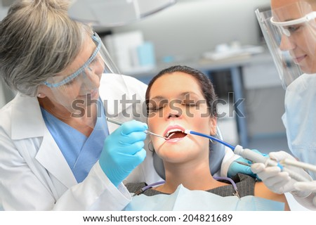 Dental check woman patient professional dentist team open mouth - stock photo