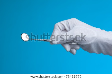 Dental checkup - dentist hand with protective gloves holding speculum (mirror)