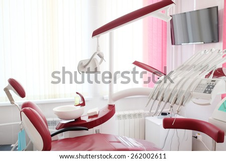 Dental clinic interior design with red chair and tools - stock photo