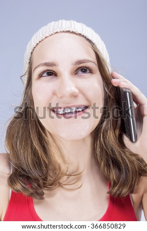 Dental Cure, Orthodontics Concept and Ideas. Blond Caucasian Teenager Wearing Teeth Braces and Speaking on Cellphone. Vertical Image