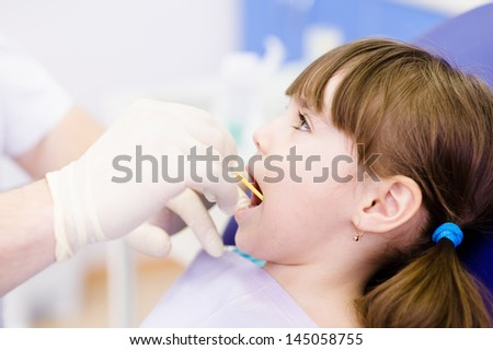 dental examining being given to little girl by dentist - stock photo