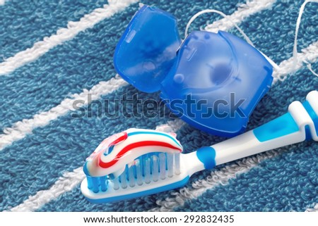Dental floss and a blue toothbrush on a towel - stock photo