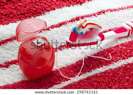 Dental floss and toothbrush on a red towel.Saturated, vivid image - stock photo