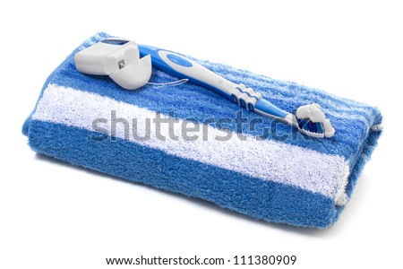 dental floss and toothbrush, towel on a white background - stock photo