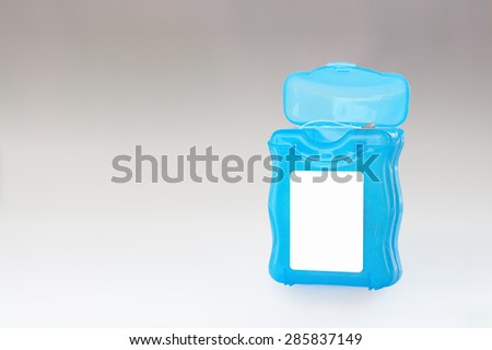 Dental floss in a grey gradient . - stock photo