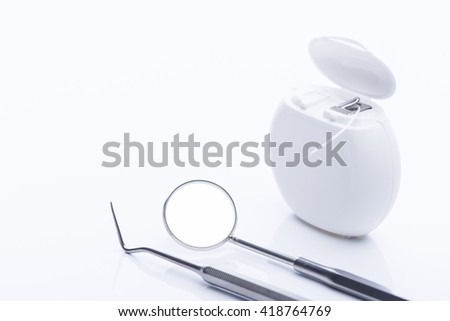 Dental floss with basic dental tools on a white surface - stock photo