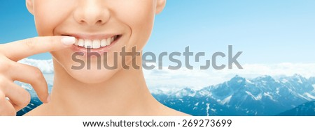 dental health, beauty, hygiene and people concept - close up of smiling woman face pointing to teeth over blue mountains background - stock photo