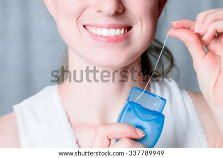 Dental hygiene and care. Dental floss. Young healthy woman face with beauty smile. Tooth brush. Oral clean, whitening. Beautiful girl. Person healthcare. Female in the morning in bathroom.  - stock photo