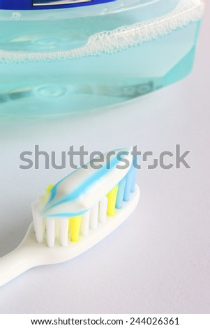 Dental hygiene with a toothpaste on a toothbrush and rinse - stock photo