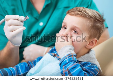 Dental inspection is being given to little boy surrounded by dentist and his assistant, and he afraid to the doctor and machine - stock photo