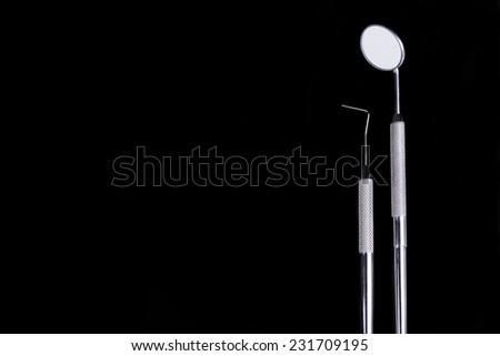 Dental instruments on black background - stock photo