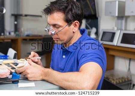 Dental lab technician applying porcelain to dentition mold - stock photo