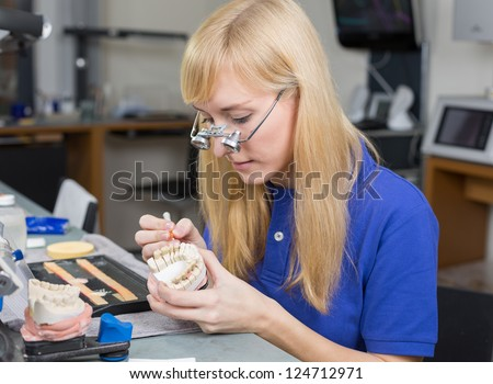 Dental lab technician applying porcelain to dentition mold in a lab - stock photo