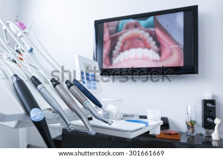 Dental office - specialist tools, drills, handpieces and laser with live picture of teeth in the background. Dental care, dental hygiene, checkup and therapy concept. - stock photo