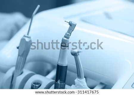 Dental professional tools and drill machine, closeup. Shallow depth and blue toned image - stock photo