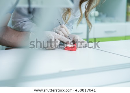 Dental prosthesis, dentures, prosthetics work. Prosthetics hands while working on the denture, false teeth, a study and a table with dental tools. - stock photo