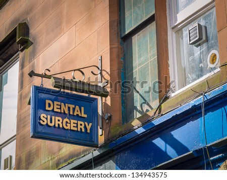 """Dental surgery office: a new small business sign with """"DENTAL SURGERY"""" spelled in bold, golden letters - stock photo"""