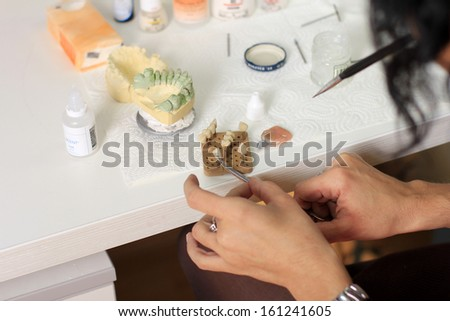 dental technician completes the process of making ceramic teeth in dental lab. Glaze. - stock photo
