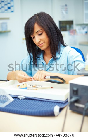 Dental technician grinding a ceramic corona in articulator - stock photo