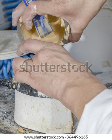 Dental technician is emptying plaster models in her lab. - stock photo