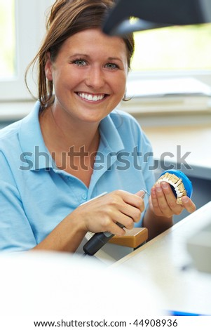 Dental technician milling a tooth for dentures - stock photo