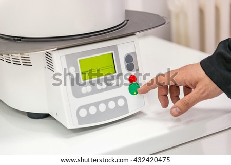 Dental technician or dentist working with tooth dentures in his laboratory. Turning on Oven and press