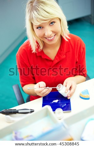Dental technician preparing ceramic powder for dentures - stock photo