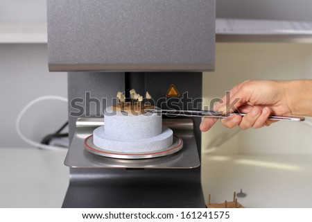 dental technician puts teeth into the oven for baking ceramics - stock photo