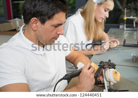Dental technician working on a dental prosthesis in an articulator - stock photo