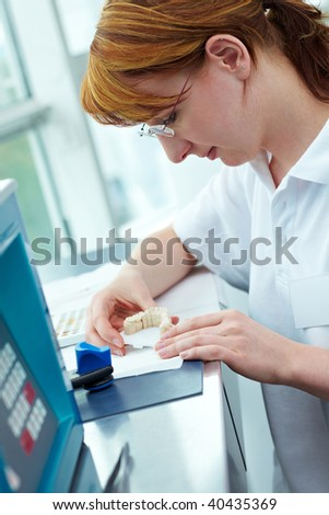 Dental technician working on ceramic coronas in a lab - stock photo
