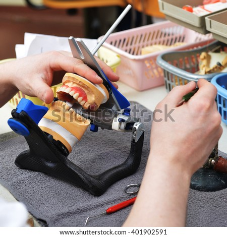 dental technician working on false teeth. table with dental tools.