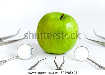 dental tools with apple on white background