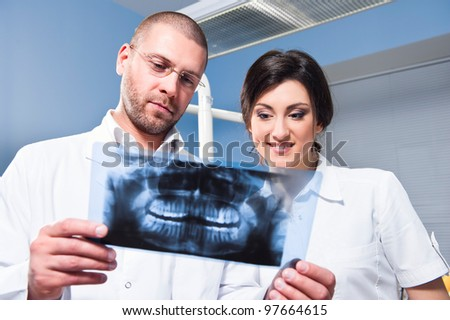 Dentist and assistant checking x-ray at dental clinic - stock photo